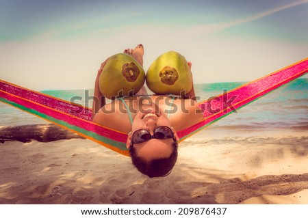 Beautiful young girl lying in a hammock on relaxing beach holding two coconuts - stock photo