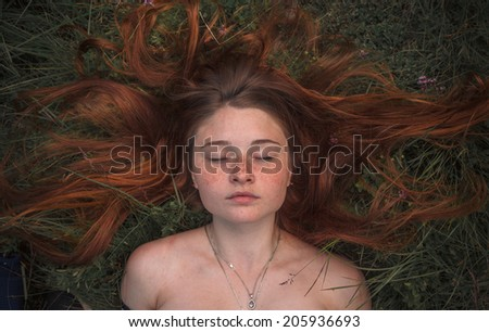 Beautiful young girl, lying in the grass. Eyes closed. - stock photo