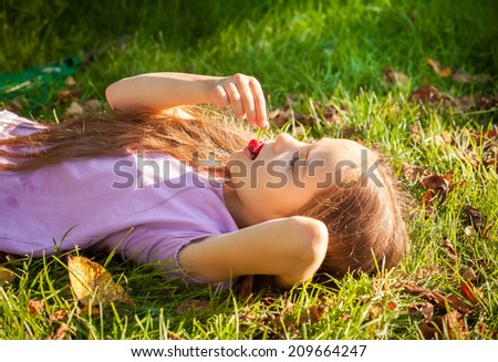 Beautiful young girl lying on grass and eating cherry outdoor - stock photo