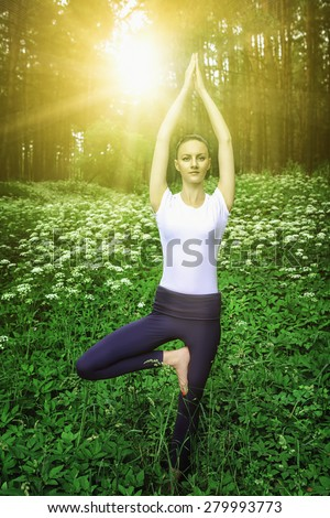 Beautiful young girl meditating in the sunrise rays in the summer forest - stock photo