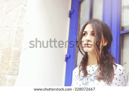 Beautiful young girl near the walls and doors. Dreamer, thoughtful girl. Space for text. Thinking about the future plans for the future. Fashionable and stylish girl. Beauty. Outdoors portrait. - stock photo