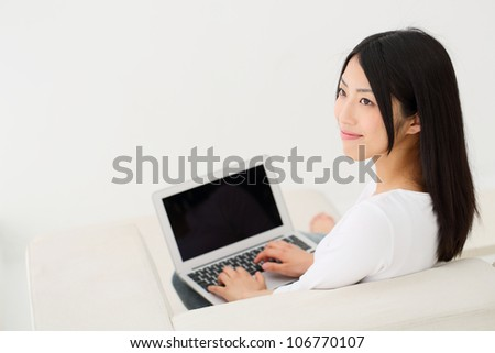 beautiful young girl on a sofa with notebook computer - stock photo