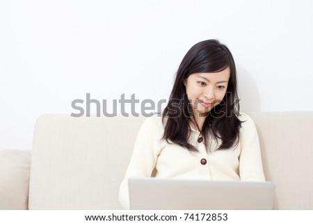 Beautiful young girl on a sofa with notebook computer. - stock photo