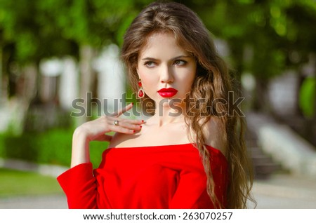 Beautiful young girl Outdoor portrait. Fashion brunette in red dress. Romantic woman posing in green park at sunny day. - stock photo