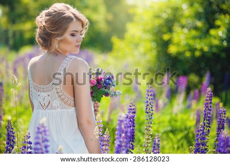 Beautiful young girl over blooming lupines - stock photo