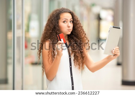 Beautiful young girl paying by credit card for shopping with a laptop against the background of the shopping center - stock photo