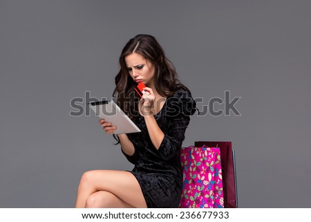 Beautiful young girl paying by credit card for shopping with a laptop and packages against gray background - stock photo