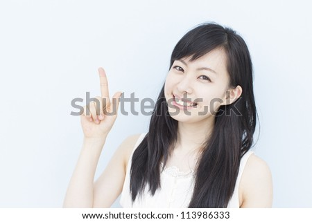 beautiful young girl pointing copy space - stock photo