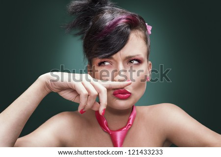 beautiful young girl putting her finger under her nose - stock photo