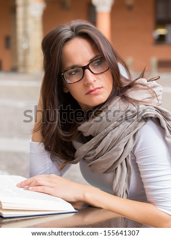 Beautiful young girl reading a book on a spring day - outdoor portrait  - stock photo