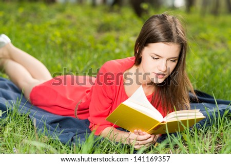 beautiful young girl reads book in park - stock photo