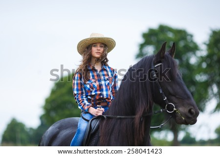 Beautiful young girl riding a horse in countryside at summer time - stock photo