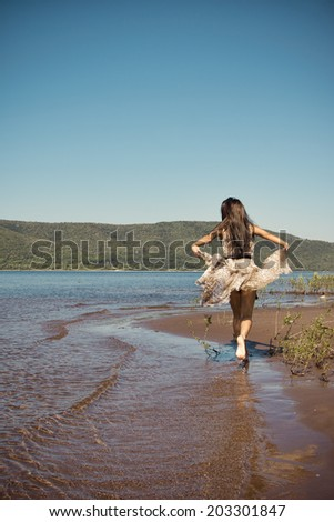 Beautiful young girl runs along the beach. Freedom concept. Rear view. Dress  waving in the wind. Unrecognizable - stock photo