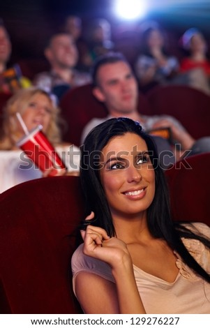 Beautiful young girl sitting in cinema, playing with hair, smiling. - stock photo