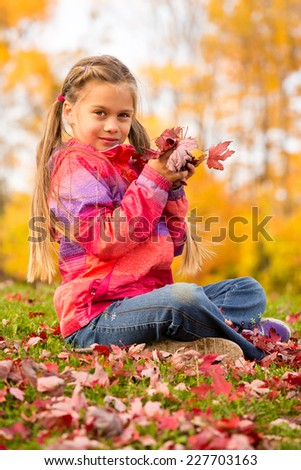 Beautiful young girl sitting on a grass with colorful autumn leaves, holding some red maple leaves in her hands - stock photo