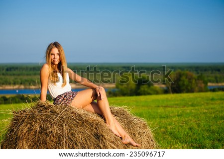 Beautiful young girl sitting on a haystack on the background of blue sky and river - stock photo
