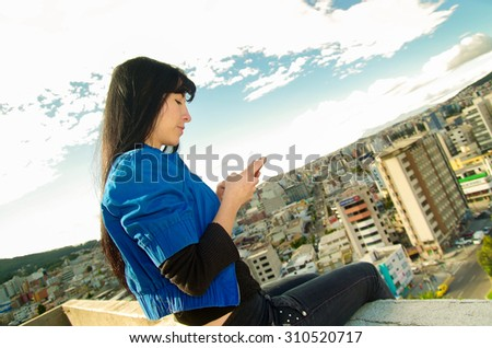 Beautiful young girl sitting on building roof edge using her cellphone - stock photo