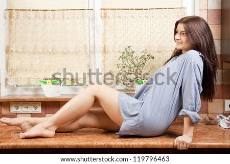 beautiful young girl sitting on table in the kitchen - stock photo