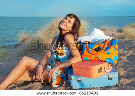 Beautiful young girl smiling and looking up. She dreams of a happy journey. She sits on the sand against the sea and next to her suitcases. - stock photo
