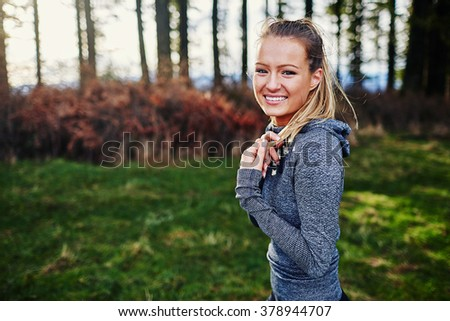 beautiful young girl smiling and walking in forest in running clothes - stock photo