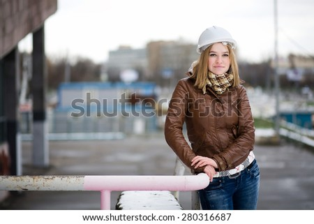 Beautiful young girl student engineer in a helmet and brown jacket works on a construction site - stock photo