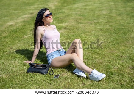 Beautiful young girl sunbathe on the grass, relaxing after work, throwing the phone and the bag aside, bright sunny day fashion style glamorous woman - stock photo