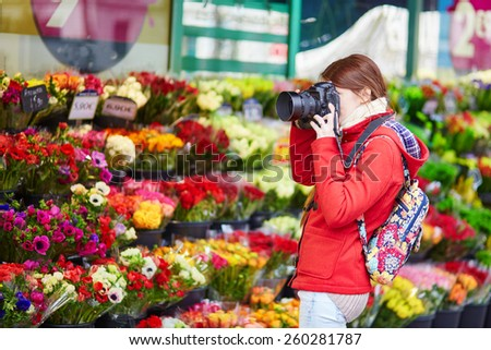 Beautiful young girl taking photo in a Parisian outdoor flower shop - stock photo