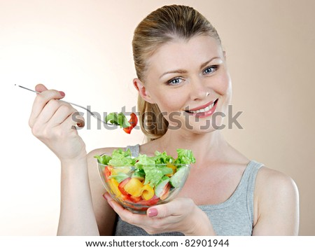 Beautiful young girl the blonde with a plate of fresh vitamin salad from vegetables - stock photo