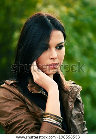 Beautiful young girl thinking in autumn park looking down - stock photo
