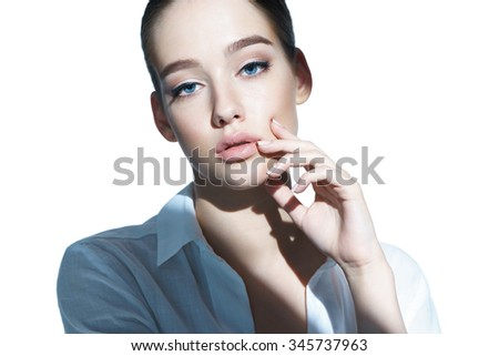 Beautiful Young girl touching her skin. Healthcare concept /  close-up of an attractive girl of the European appearance in a white shirt - isolated on white background - stock photo
