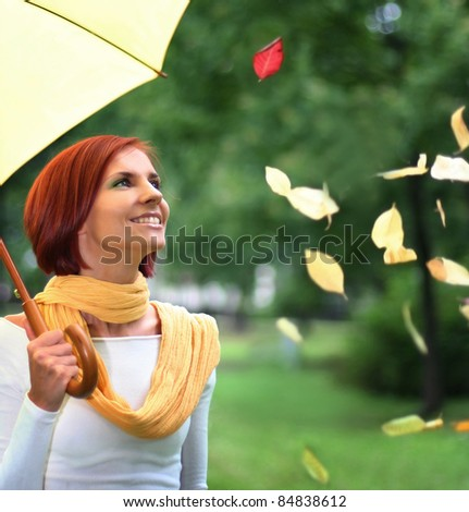 beautiful young girl under yellow umbrella in the autumn park - stock photo