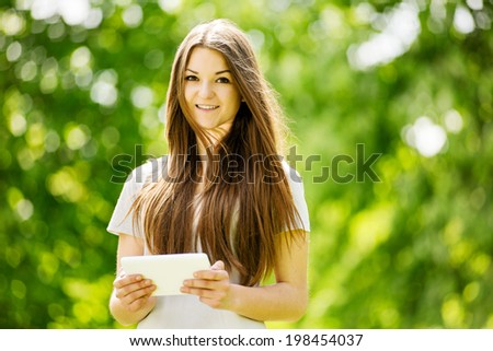 Beautiful young girl using a tablet computer in a leafy green park navigating the touchscreen with her finger , with copyspace - stock photo