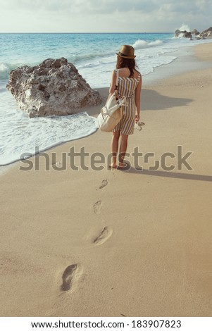Beautiful young girl walking on the beach - stock photo