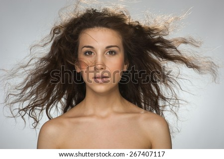 Beautiful young girl waving her hair on gray background - stock photo
