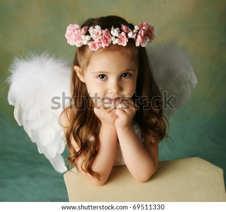 Beautiful young girl wearing angel wings and flower halo with smile happy expression - stock photo