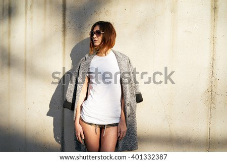 beautiful young girl wearing in a white blank t-shirt and sunglasses posing against a background of a concrete wall in the rays of the setting sun - stock photo