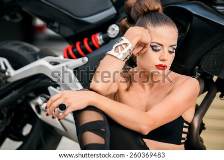 Beautiful young girl with a fashionable hairstyle and red lips poses next to motorcycle - stock photo