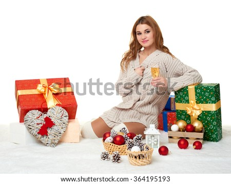 beautiful young girl with a glass of champagne and gift boxes on white - stock photo