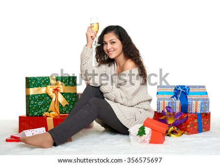 beautiful young girl with a glass of champagne and gift boxes, white background - stock photo