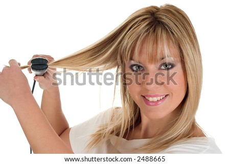 Beautiful young girl with a hair straightener, on white background - stock photo