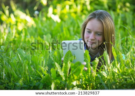 Beautiful young girl with a tablet PC lying in the grass. - stock photo