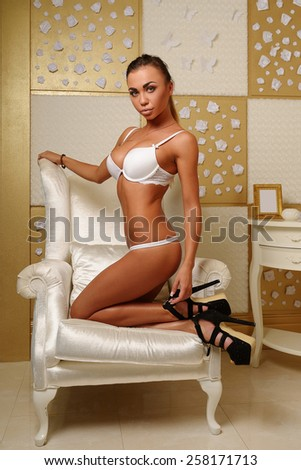 Beautiful young girl with big breasts, full lips, straight hair, in a candid white underwear, athletic, tanned, in a white lounge chair in the interior of the hotel on the background gold and white - stock photo