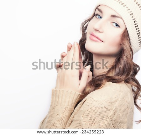 Beautiful young girl with blue eyes in winter wool hat and sweater. Isolated. Copy space. - stock photo