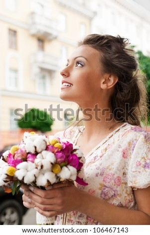 beautiful young girl with bouquet of flowers. Outdoors - stock photo