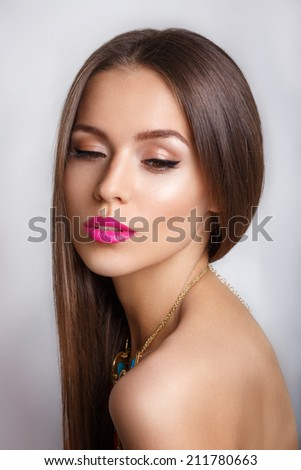 Beautiful young girl with bright pink lips and a professional make-up with a necklace - stock photo