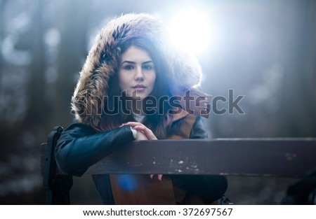 Beautiful young girl with brown fur cape enjoying the winter scenery sitting on the bench in park. Teenage girl posing, winter concept. Young female with snowflakes around in bright cold day - stock photo