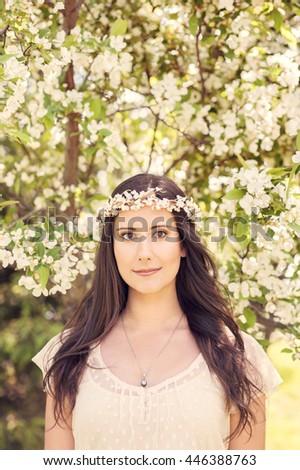 Beautiful young girl with brown hair in a white wedding dress. Bridal portrait with a flower crown, fruit tree blossoms in the background. - stock photo