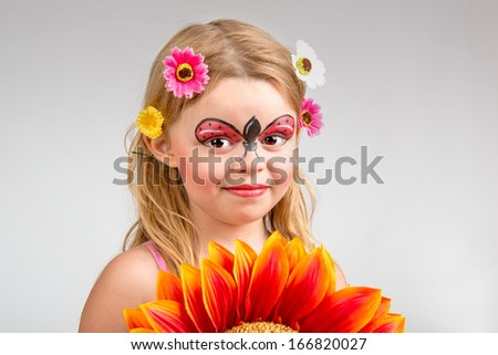 Beautiful young girl with face painted like a ladybug - stock photo