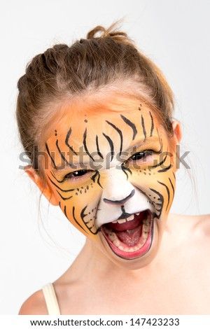Beautiful young girl with face painted like a tiger - stock photo