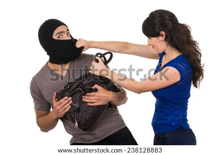 beautiful young girl with hand bag punching masked male thief beautiful young girl with hand bag isolated on white - stock photo